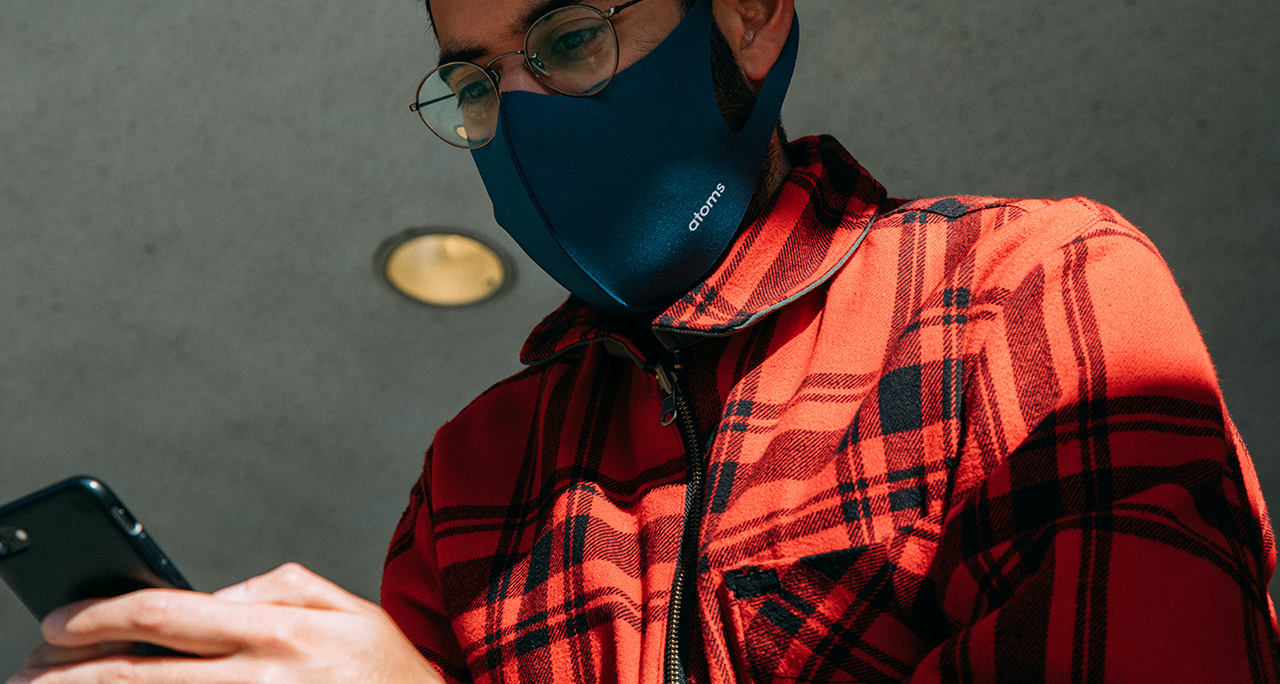 person in mask using smart phone and facial recognition